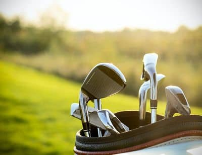 this is an image of Golf clubs drivers over green field background. Summer sunset